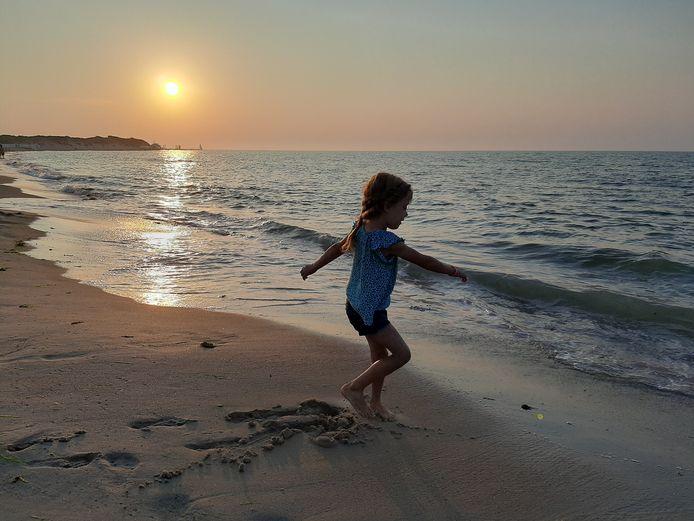 De winnende foto waarop Jula aan het eind van de dag richting golven danst aan het strand van Vrouwenpolder.