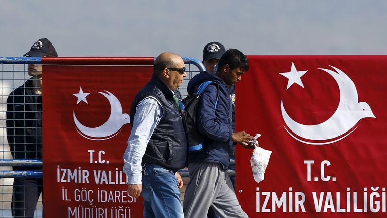 Een migrant die is teruggestuurd vanuit Griekenland wordt door een Turkse politieman begeleid in de havenstad Dikili. Beeld reuters