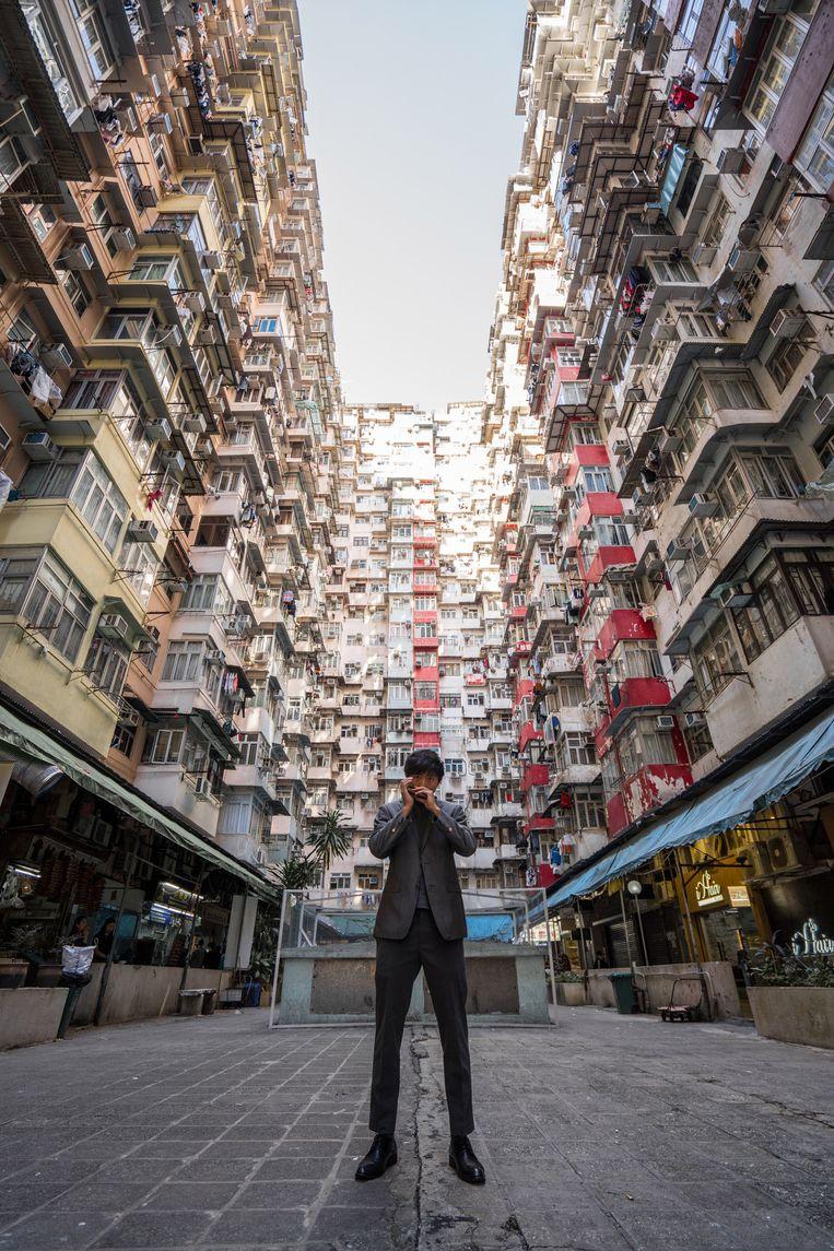 CY Leo speelt tussen de flats in Hongkong. 'We maken geen Hongkongse kunst meer, maar proberen in de gunst te komen van China. We verliezen onze eigenheid.' Beeld Isaac Woo