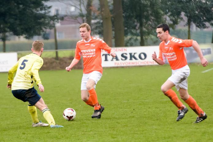 Jasper Beerten aan de bal namens Budel. Rechts teamgenoot Rik Bogers en links verdediger Roy van de Putten van MULO.
