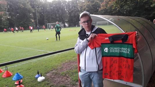 Vrijwilliger Chiel ter Haar van de Stichting Football Makes It Happen met een door spelers gesigneerd shirt van NEC.