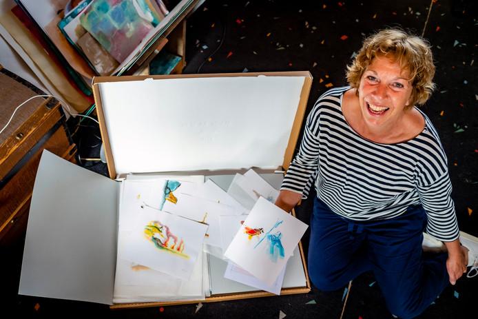 Els van Egeraat op haar zolder met één van de vijftien dozen. Zij geeft haar illustratie-collectie aan het Literatuurmuseum.