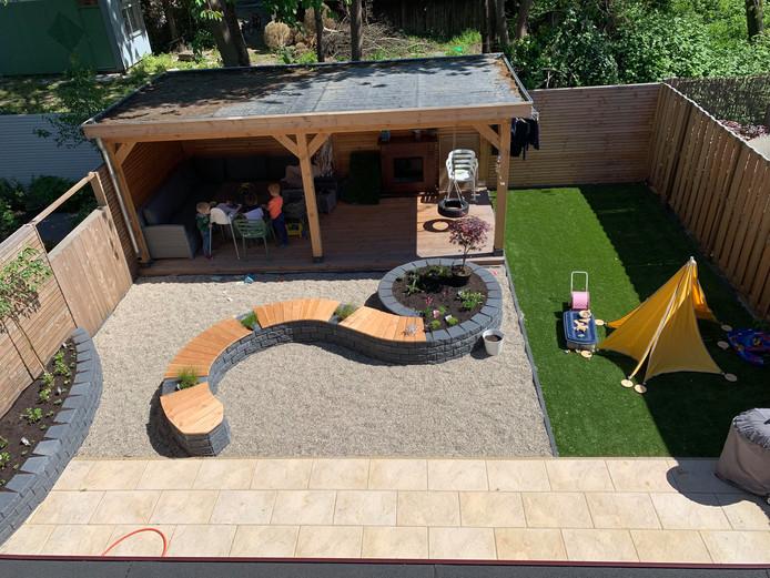 Strakke lijnen en achter in de tuin een riante overkapping voor speeltoestellen en een eettafel.