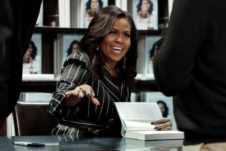 Michelle Obama is druk aan het signeren.