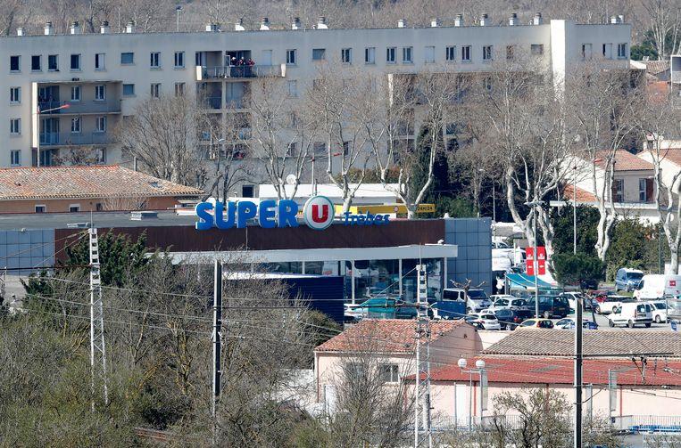 De Super U in Trèbes waar de gijzeling plaatsgrijpt. Speciale eenheden van de politie zijn aanwezig, onder meer op de bovenste verdieping van het achterliggende appartementsgebouw.