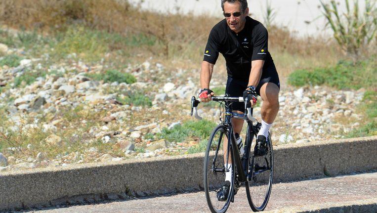 © ANP De Franse president Sarkozy op zijn fiets. Beeld
