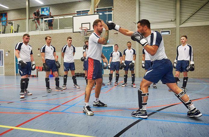 Leerlingen tijdens het sporten als onderdeel van de opleiding tot beveiliger op vliegbasis Volkel. Op de foto geeft sergeant Haroen Salwegter (linksvoor) uitleg over vechttechnieken.
