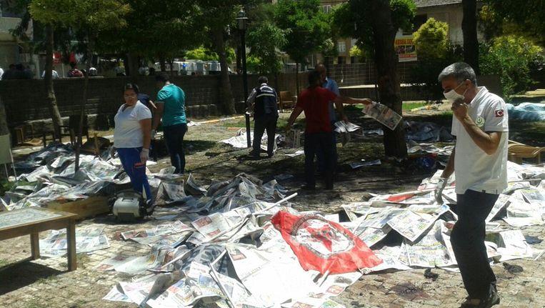 De tuin waar de aanslag plaatsvond. de doden zijn bedekt met kranten. Beeld afp