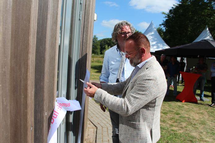 Zorgondernemer Erik Zwoferink (voor) en investeerder Roelof Bijlsma openen door het doorknippen van een lint Domus Dulcis Domus op het Leo Stichting-complex bij Borculo.