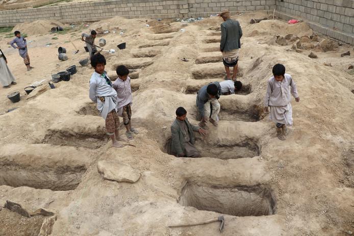 Jongens inspecteren de graven voor de slachtoffers van de luchtaanval in Jemen.