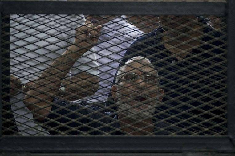 De gevangen leider van de Moslimbroederschap Mohamed Badie gebaart vanuit zijn kooi naar andere leden van de verboden beweging. Beeld afp