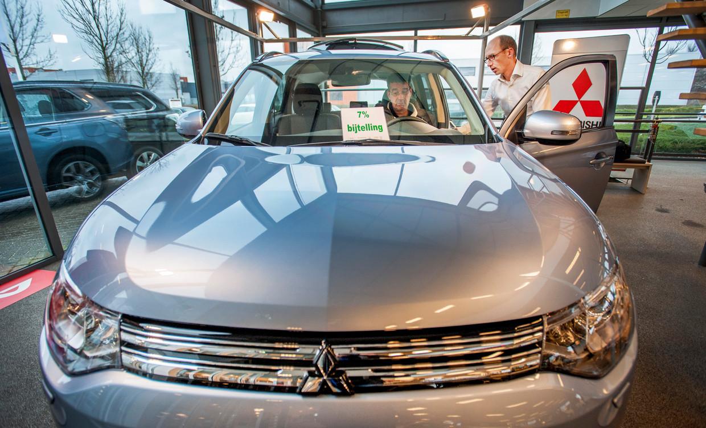 Een potentiële koper van een Mitsubishi Outlander krijgt in 2013 in een showroom in Hoofddorp uitleg van een verkoper.