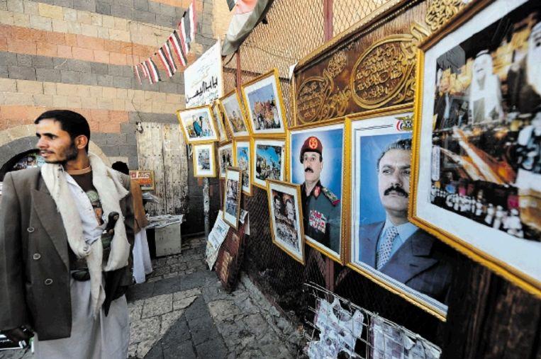Een stamhoofd voor een rij portretten van de Jemenitische president Saleh. (FOTO EPA) Beeld EPA