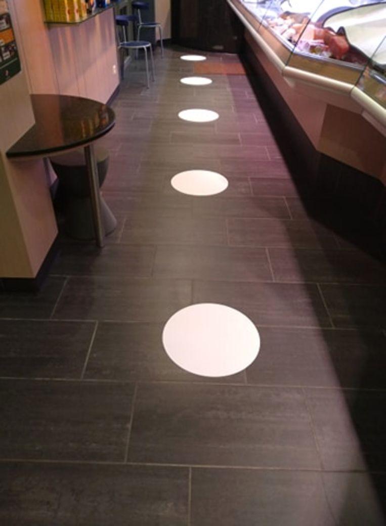 De witte bollen tonen klanten wat 1,5 meter afstand is.