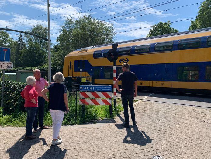 Walther Hoosemans in gesprek met twee buurtbewoonsters over treinen. Spoorovergang Dorst Wethouder van Dijklaan.