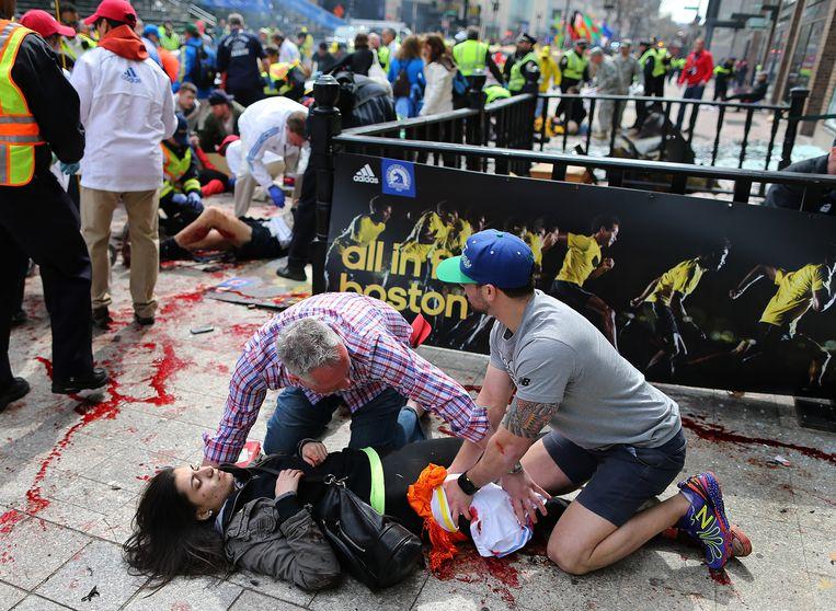 Een gewonde vrouw wordt geholpen na de bomexplosies. Beeld AP