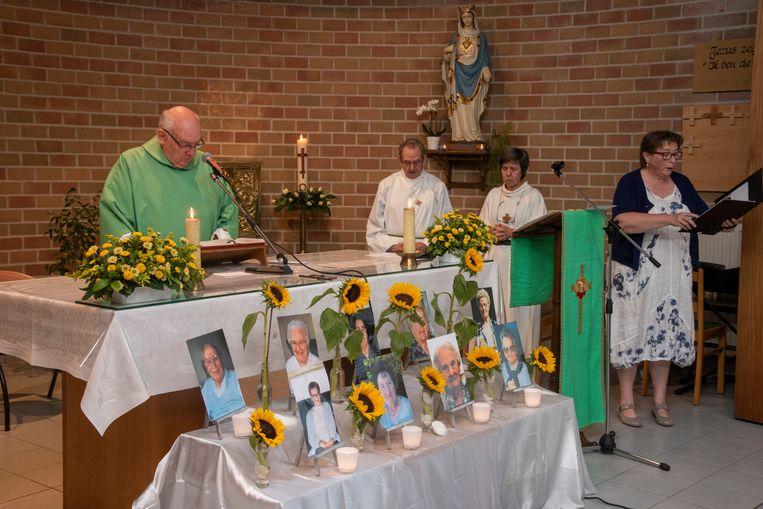Foto's van de negen slachtoffers aan het altaar tijdens de herdenking van de brand in Kanunnik Triest.