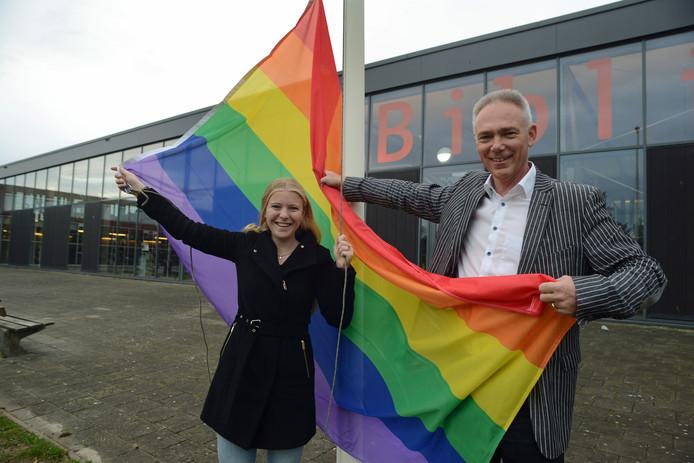 Mirte Zwier en rector Peter van der Gaag hijsen samen de regenboogvlag op Pontes Pieter Zeeman in Zierikzee