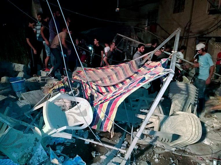 Mensen zoeken naar overlevenden tussen het puin nadat een wapendepot ontplofte in Sadr-stad in Baghdad.