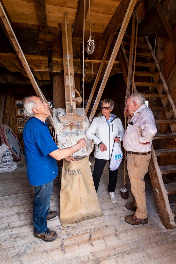 De molenaars Gerard Gerrits (blauw shirt) en Ton van den Boom geven uitleg over de werking van de molen.