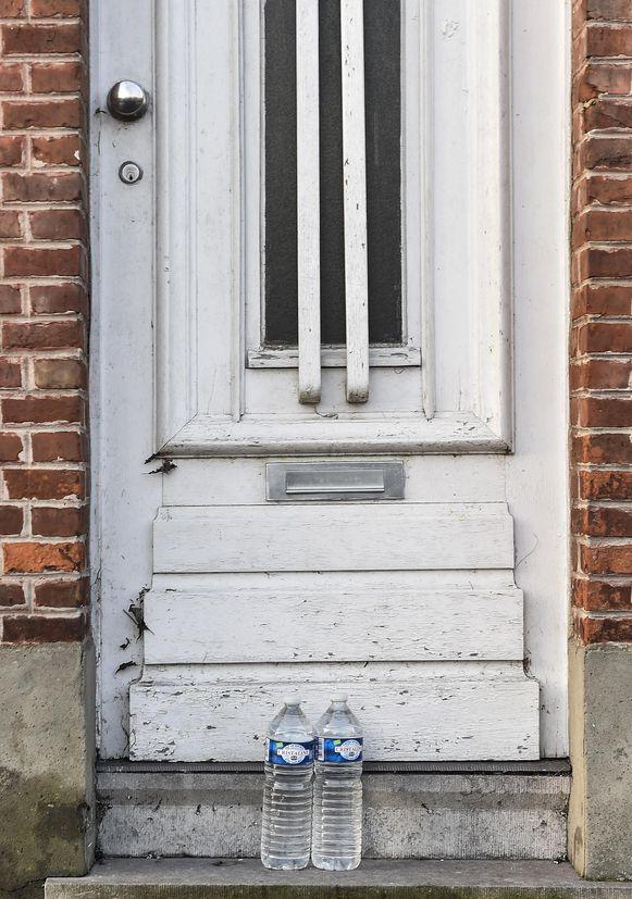 Bij ieder huis stonden er twee flessen water voor de deur.