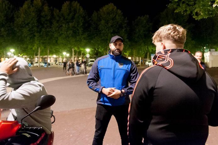 Ismail in gesprek met een groepje jongeren.