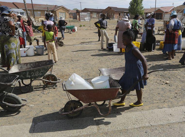 Inwoners staan in het Senekal, Zuid Afrika, in de rij voor water dat door hulpverleners wordt uitgedeeld, 11 January 2016 Beeld DIO