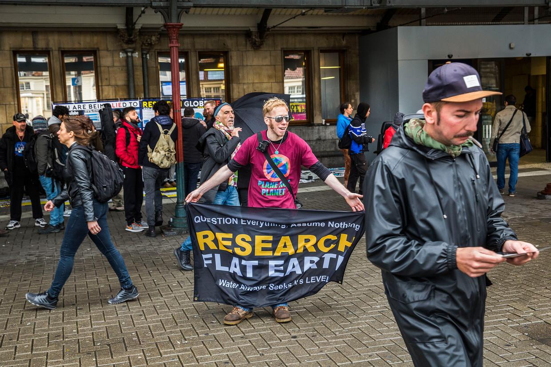 Mensen die geloven dat de aarde plat is kwamen dit weekend samen in Amsterdam. Op het centraal station in Amsterdam delen ze flyers uit.