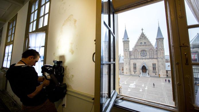 Journalisten, cameramensen en fotografen maken opnames van het achterstallig onderhoud bij het Binnenhof-complex.