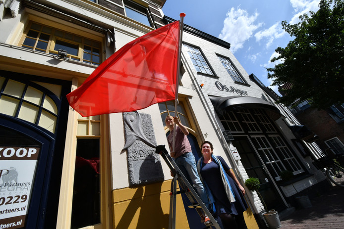 Voorzitter van de jongerentak Jesse Koops (met vlag) en landelijk PvdA-voorzitter Nelleke Vedelaar voor het gebouw in Zwolle waar de SDAP 125 jaar geleden werd opgericht.