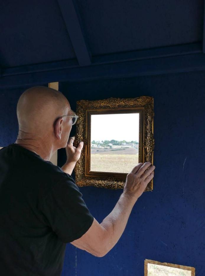 Arno Arts kijkt door in zijn museum door een lijst naar het landschap. Foto: Véronique Sabadel.