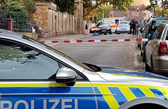 De plek waar de schietpartij plaatsvond in Halle. Voor de synagoge ligt een slachtoffer, bedekt met een blauw laken.