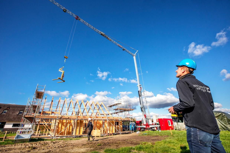 Ecologisch aannemer Jan-Willem van Engen bedient een elektrische kraan op een bouwterrein in Wageningen waar nagenoeg  stikstofvrij wordt gebouwd. Beeld Raymond Rutting / de Volkskrant