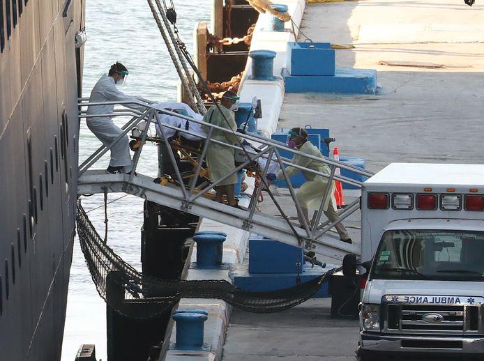 Een patiënt wordt door ambulancepersoneel van boord van de Zaandam gehaald in de haven Port Everglades in Fort Lauderdale, Florida.