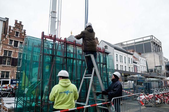 Met behulp van een metershoge kraan worden de verschillende onderdelen van de constructie over de gevel getild.