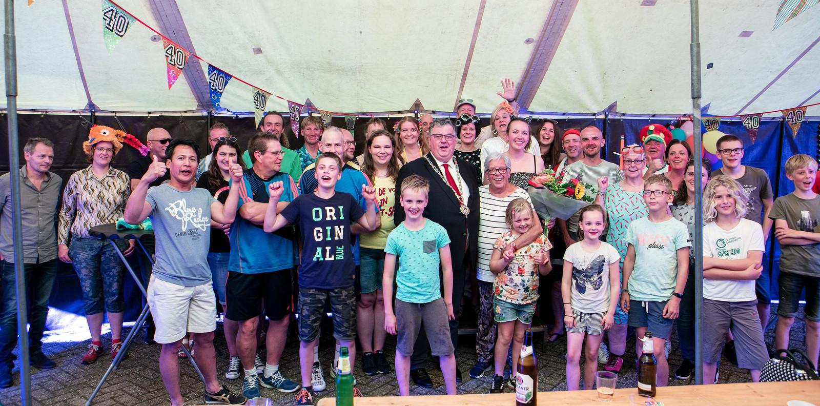 Ans Rikken (met bloemen) naast burgemeester Bruls en omringd door leden van 'haar' badmintonvereniging 't Pluumke-Lent.