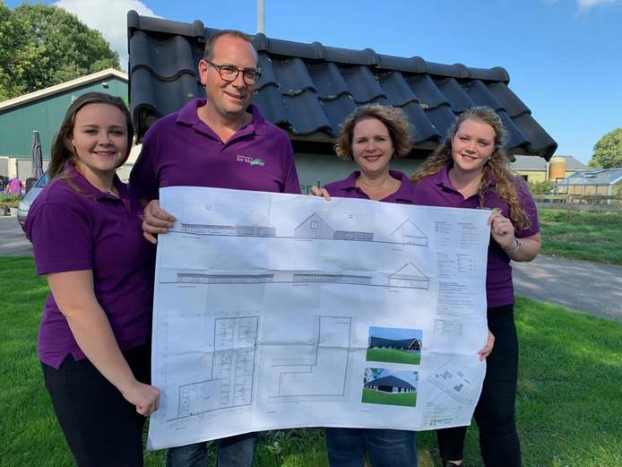 Britt, Marcel, Monique en Maud de Kok (van links naar rechts) met het ontwerp van de nieuwbouw bij zorgboerderij De Maashof in Maasbommel.