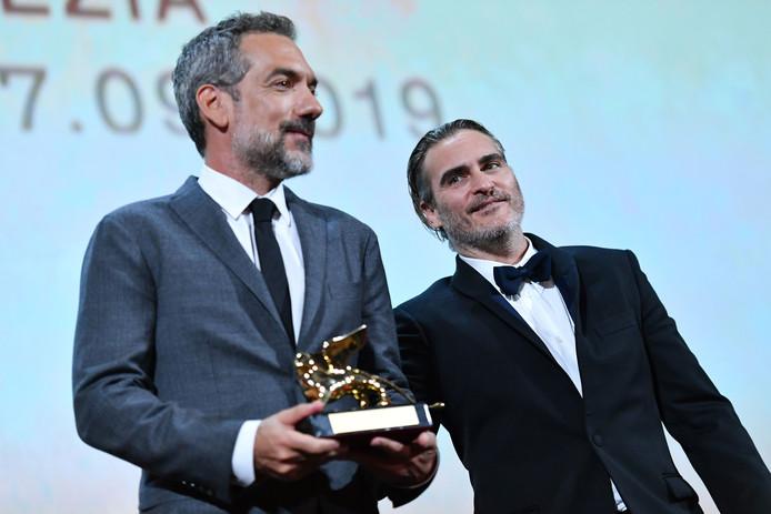 De Amerikaanse regisseur Todd Phillips (L), geflankeerd door acteur Joaquin Phoenix, met in zijn handen de Gouden Leeuw.