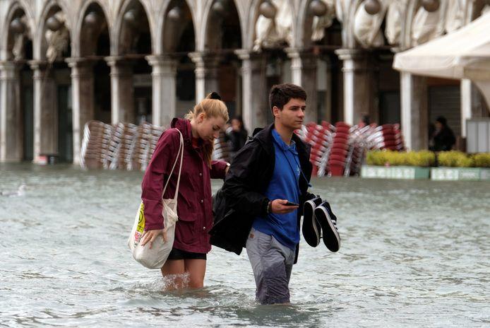 Toeristen waden door het ondergelopen San Marco-plein.