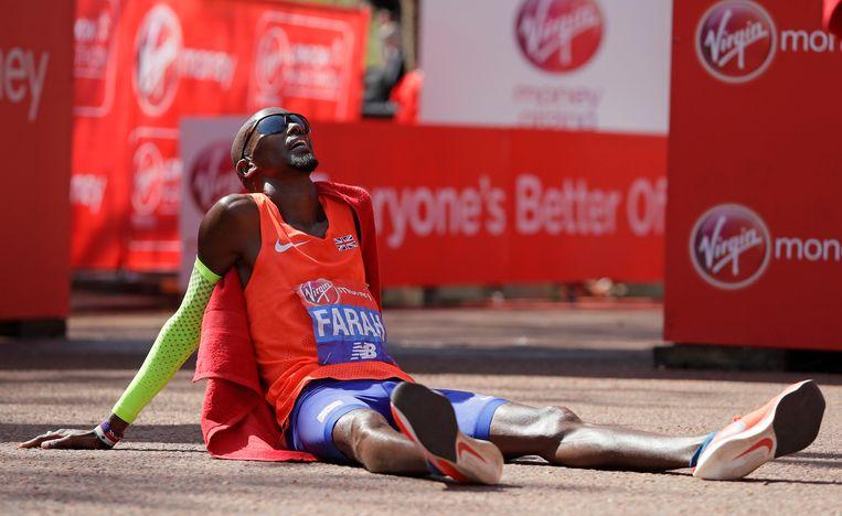De Brit Mo Farah hijgt uit nadat hij op de marathon van Londen als derde over de finish is gegaan. Beeld AP