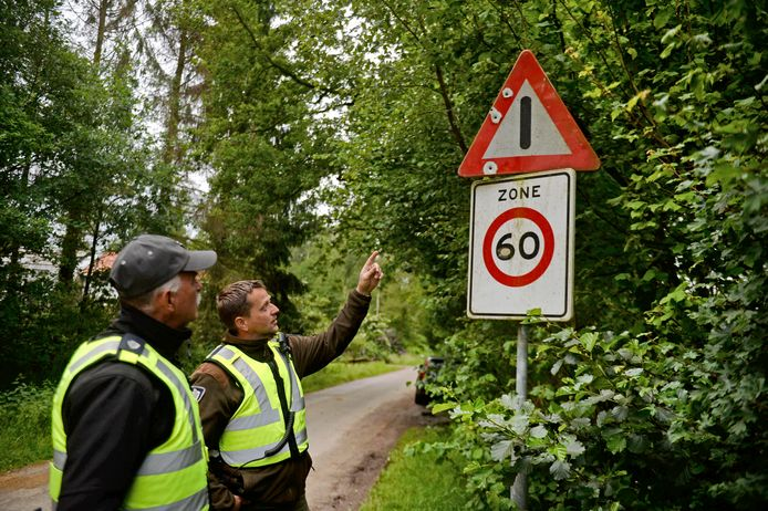 Jarno Wesselink en Wim Kutterik, groene boa's van het Landschap Overijssel, wijzen op een verkeersbord. Daar heeft iemand een wapen op getest.