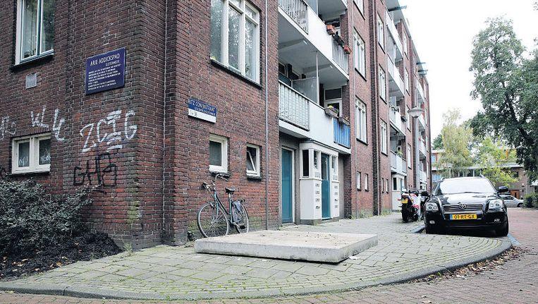 Een betonnen plaat dekt de plek af van de vuilcontainer in de Fritz Conijnstraat, die is meegenomen voor sporenonderzoek. Beeld ANP