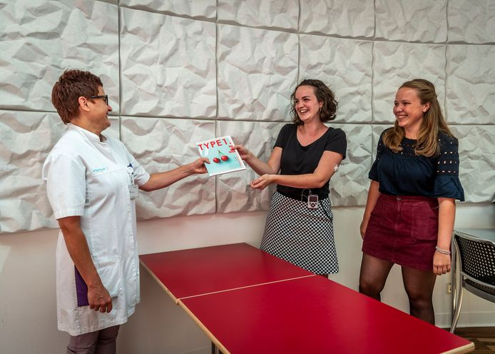 Anne Jacobs (met tijdschrift) en Sanne van Beem overhandigen het tijdschrift aan Mirjam van de Weijer.