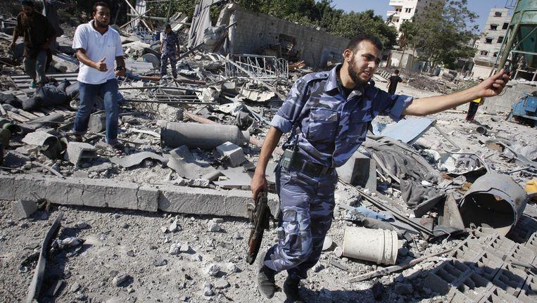 Een Hamaslid loopt over de overblijfselen van een trainingskamp dat eerder door Israelische troepen is platgegooid. Beeld ap