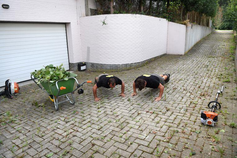 Tuinmannen drukken zich op bij het huis waar Verstappen met zijn ouders woonde, voor de scheiding. Beeld Marcel van den Bergh / de Volkskrant
