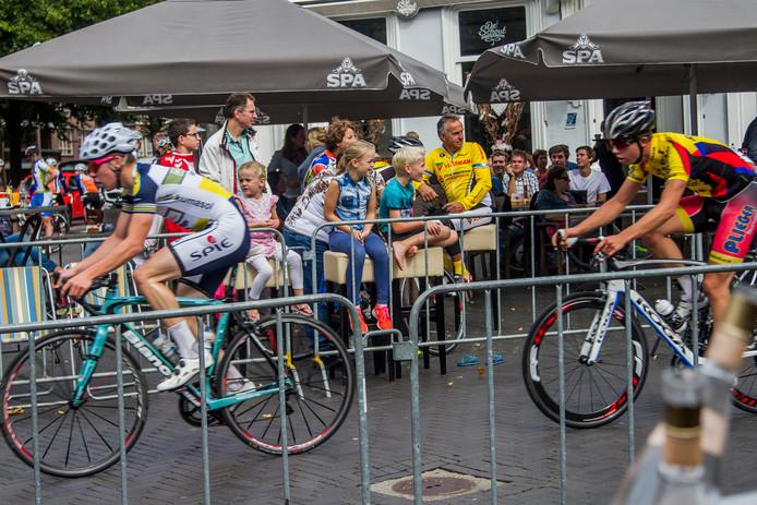 Toeschouwers juichen de wielrenners toe op de Oosterhoutse Markt tijdens de wielerronde Hart van Oosterhout.