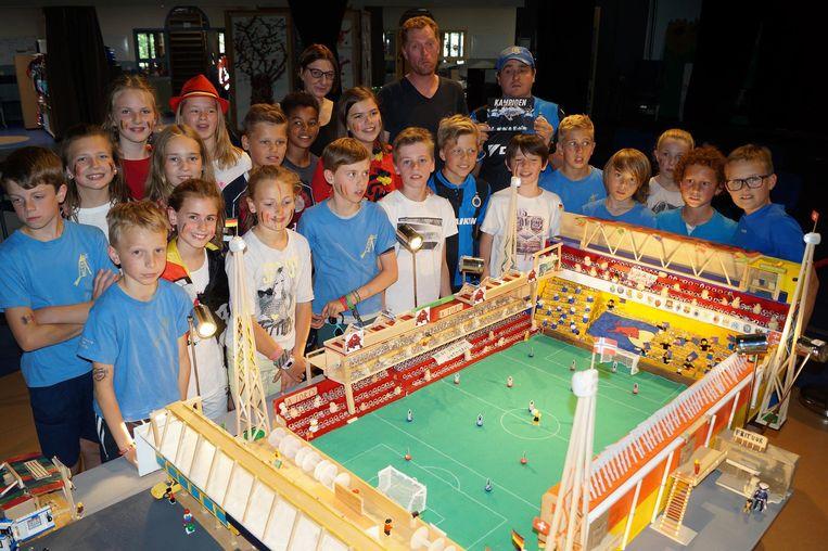 Andy De Wilde (met pet) van Mivalti toont samen met de leerlingen van Reuzenhuis trots de maquette.