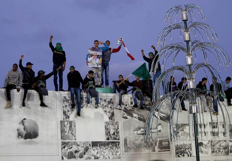 Aanhangers van Kadhafi vormen een menselijk schild rondom het huis van de Libische leider. Beeld reuters