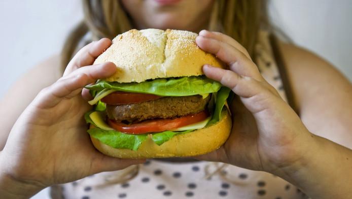 Meisje eet hamburger.