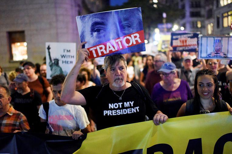 Tegenstanders van president Trump protesteren maandag in New York met pamfletten waarop 'Verrader' staat. Ook aanhangers van Trump gingen de straat op tijdens zijn bezoek aan de VN. Beeld REUTERS